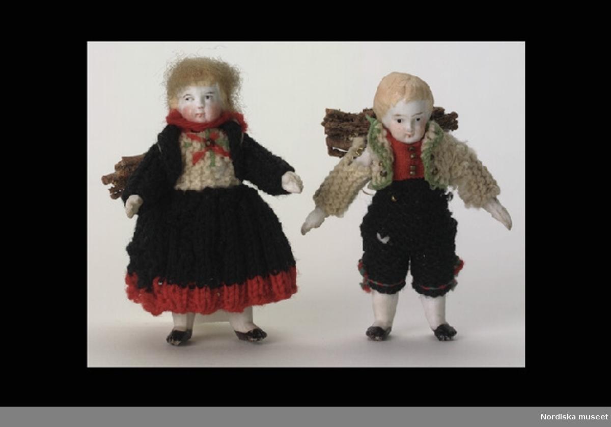 """Huvudliggaren: """"a-b 2 dockor, 1 manlig och 1 kvinnlig, små, iklädda stickade kläder, båda med risknippa på ryggen, antagligen från Holland. Gåva 10/12 1910 Silfwerswärd Ch., fru, f. Schartau, Stockholm."""""""