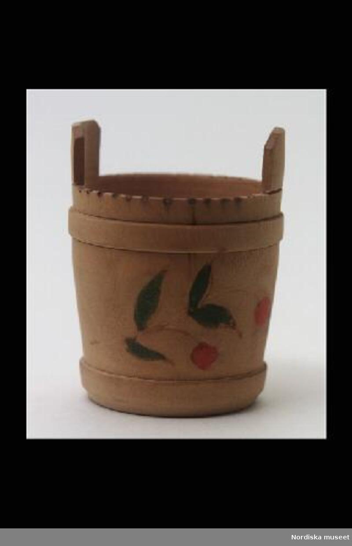 """Inventering Sesam 1996-1999: H 4   Diam 3 (cm) Bytta, till dockskåp, av trä, svarvad, imiterande laggkärl, runt med två uppstående lagg, två """"träband"""", glödritad kant. Målad dekor föreställande två röda bär/blommor samt gröna löv. Tillhör köket i dockskåp 219.377. Har brukats av frk Greta af Billbergh, f. 1889, dotter till ingenjör Otto af Billbergh och hans fru Hildur, f. Levin. Bilaga  Charlotta Dobson Hoffman nov 1997"""