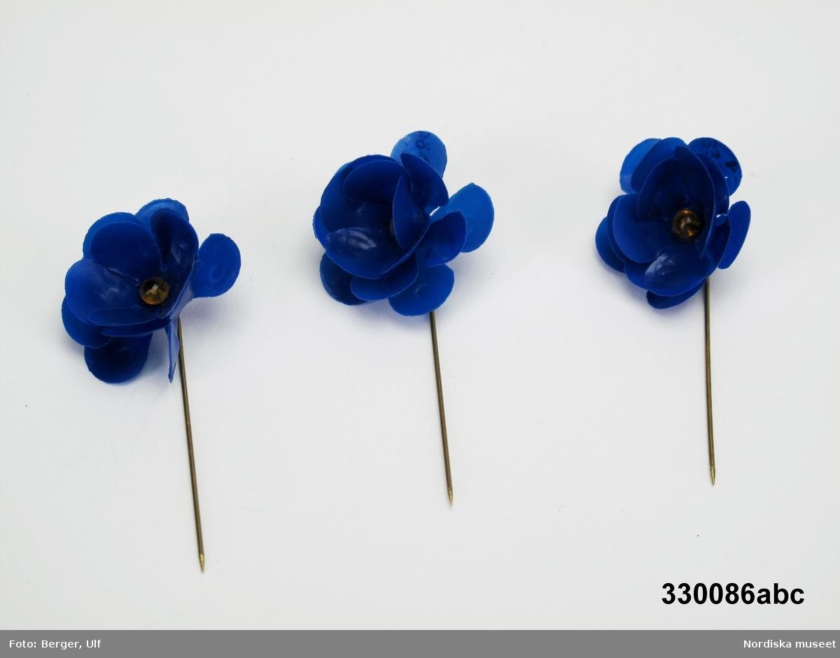 Majblomma, 3 st (a-c), mörk koboltblå, med bärnstensgul mittknapp av glas och nål av gulmetall. Blomman är tredubbel och tillverkad av celluloid. c) saknar ett kronblad i yttre kransen.  Detta är den 1:a majblomman från år 1907 /Lena Kättström Höök 2008-11-17