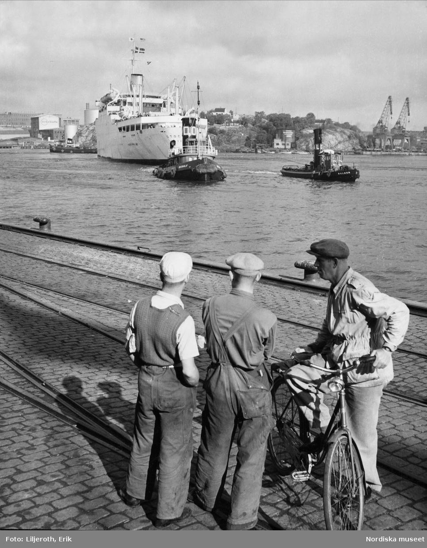 Tre hamnarbetare tittar på Svenska Amerika Liniens passagerarfartyg M/S Stockholm på väg in i Göteborgs hamn