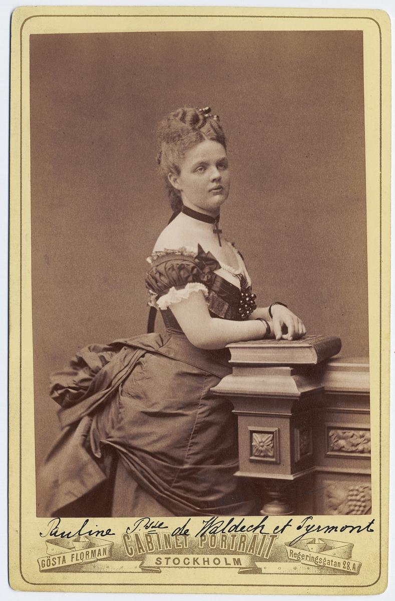 Kabinettsfotografi. Porträtt av prinsessan  Pauline av Waldeck och Pyrmont (1855-1925) iklädd  urringad klänning med turnyr och kort puffärm. Dekorerat dekolletage. Runt halsen bär hon ett band vid vilket ett kors är fäst.1870-tal.