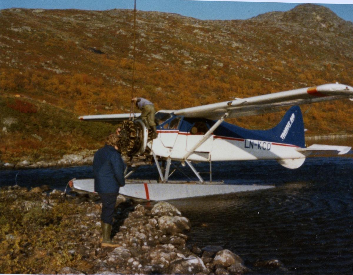 Landskap. Ett fly , LN-KCQ, DHC-2 Beaver, ved vannkanten. Motorbytte.