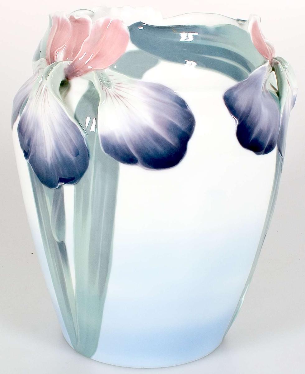 Vas av porslin, vitglaserad med underglasyrmålning i grönt, blålila och brunrosa. Instäplat i massan WL 90025, tryckt stämpel: Rörstrand KL.