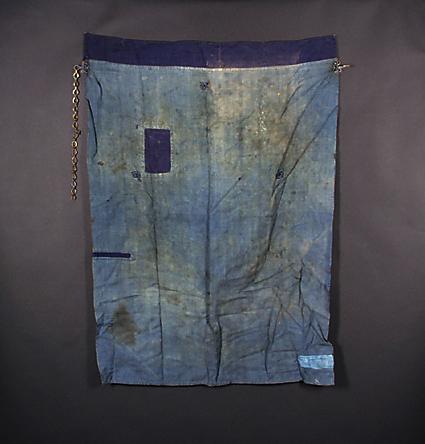 """Ljusblått bomullsförkläde med olikfärgade lappar. Mässingskedja som """"midjegördel""""."""