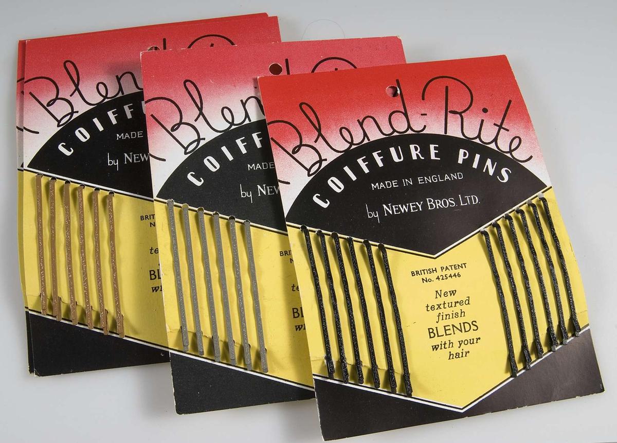 Pappask innehållande hårspännen uppsatta på originalpapper. Förpackningen är röd/vit/svart och innehåller 14 papper med 12 smala hårspännen i två olika färger på varje. På asken tryckt text: Blend Rite COIFFURE PINS. På varje papper tryckt 40 öre.