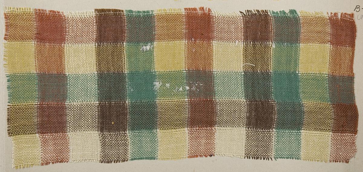 Rutigt gardintyg i brunt, beige och grönt. Tyget är vävt i tuskaft. Tygprovet har nummer B2118.