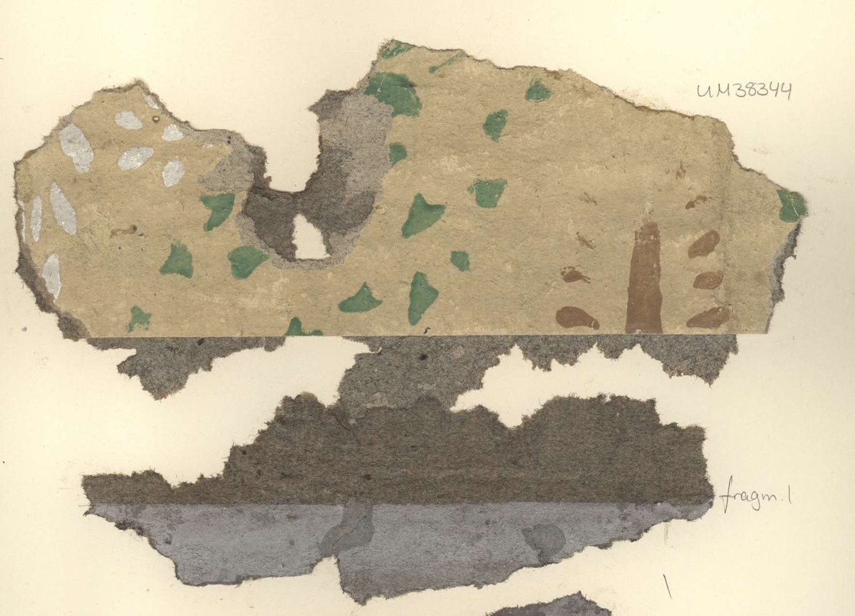 Fragment av tapet av papper, schablonmålad, beige bottenfärg med mönster i grönt, vitt och brunt. Fragmentet märkt med siffran 1.