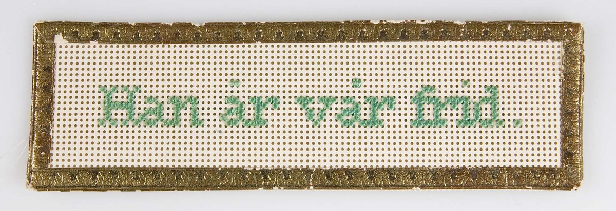 Rektangulärt bokmärke i genombrutet papper med guldbård. Baksidan består av vitt tyg. På det genombrutna pappret har man i grönt broderat texten: Han är vår frid.