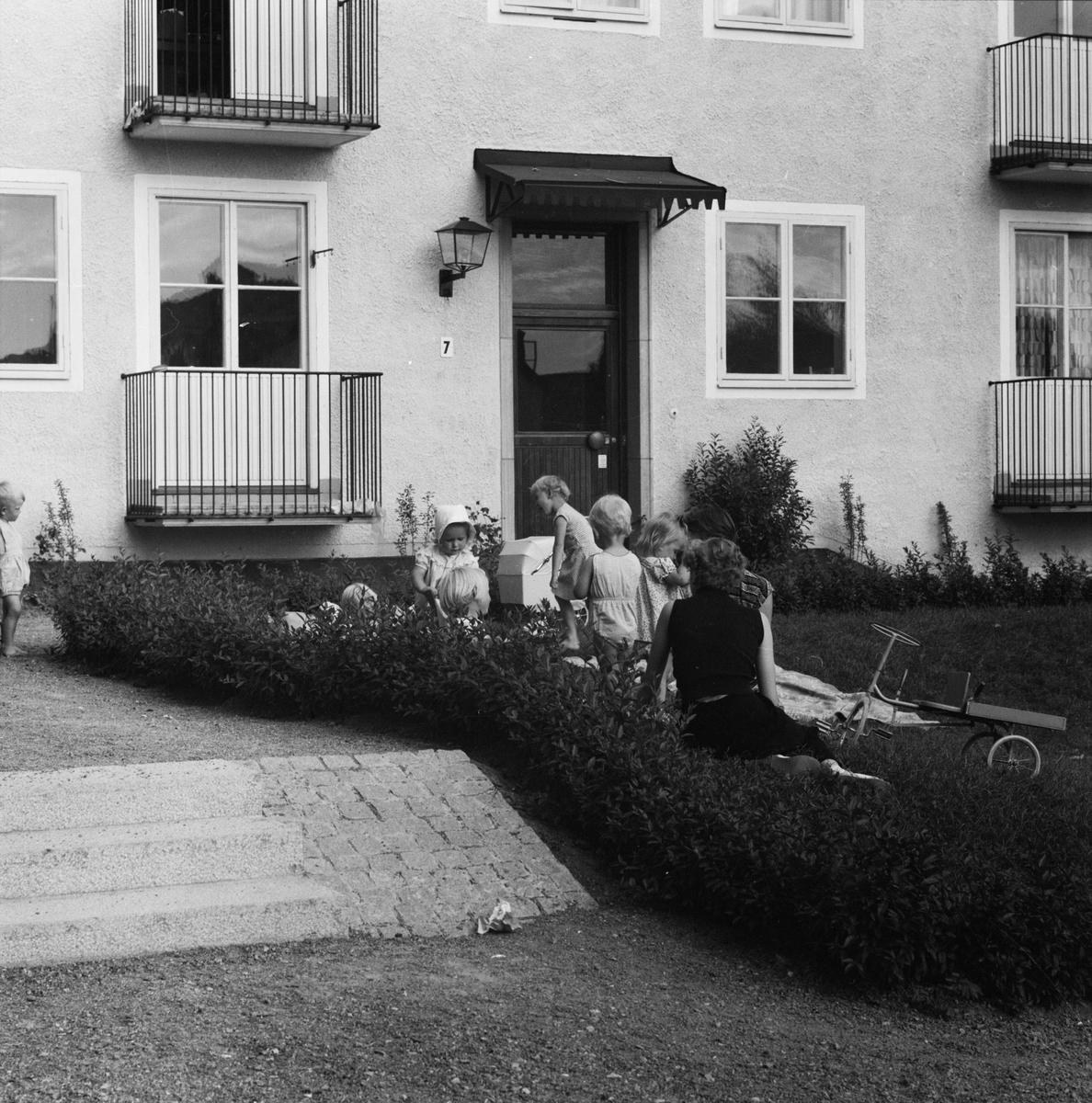 Barn och vuxna utanför flerbostadshus, Studentstaden, Rackarberget, Uppsala