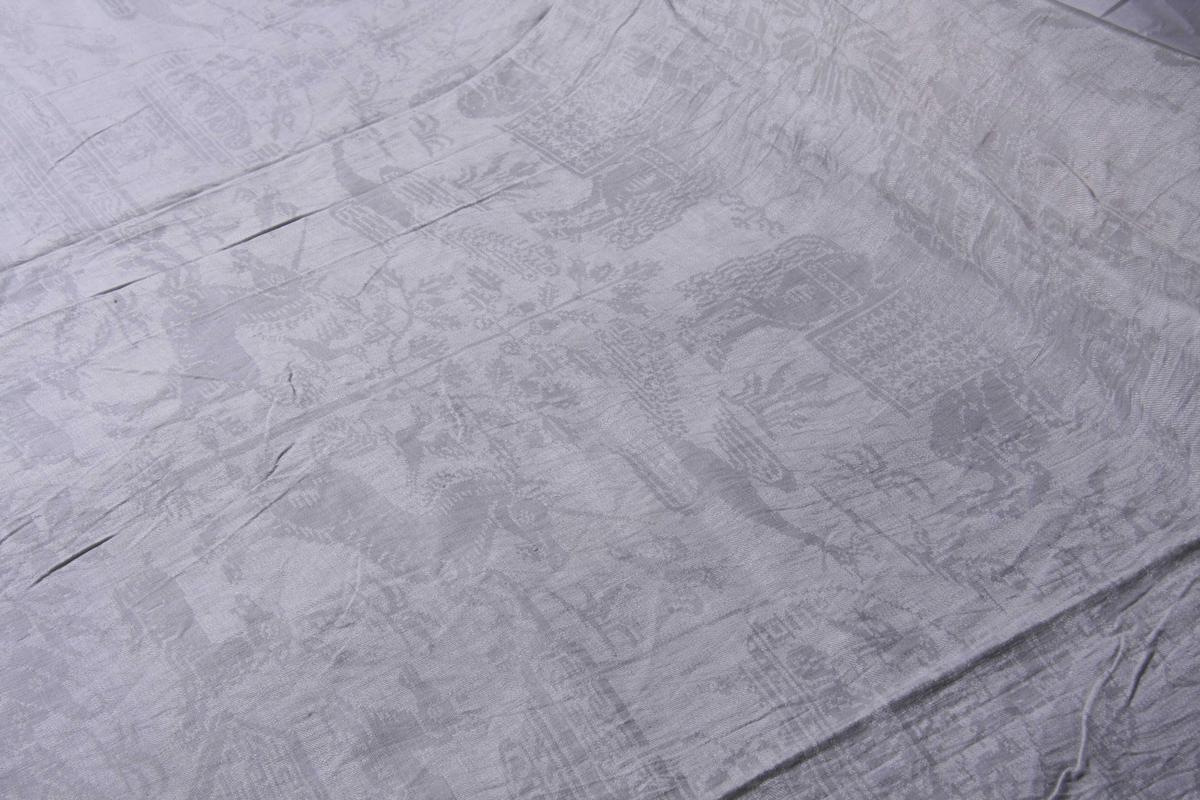 Hvit lindamask med mønster: Enhjørninger flankerer fontene stående på bakbenene med liggende hjerter og andre dyr omkring. Damer til hest med hatt på hodet. Duken har smal fall på kortsidene.