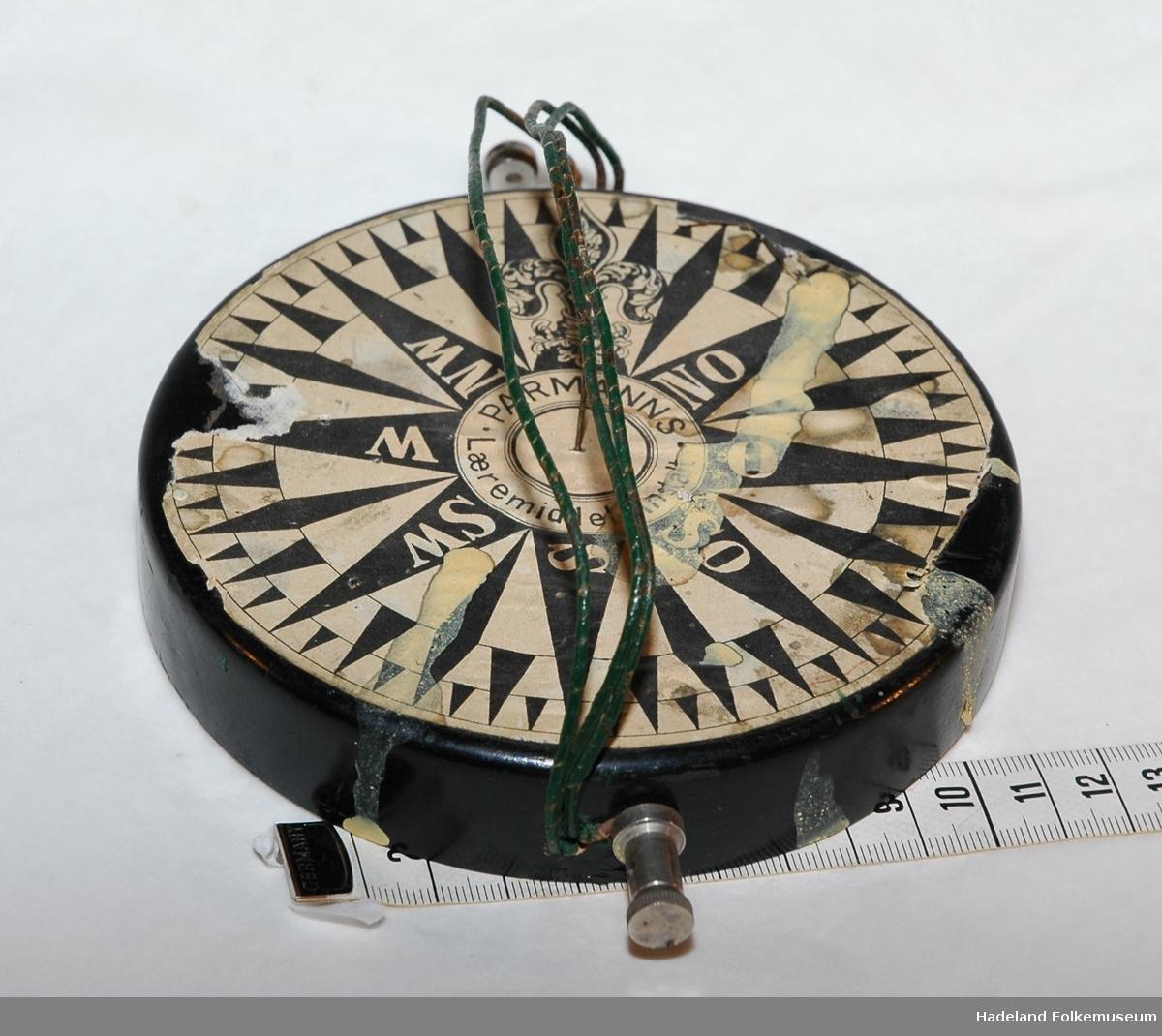 Rund treplate med metallbånd over. Kompassnål mangler.