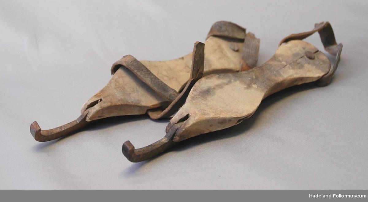 Jernmeien er krum foran og formet til et øye m/ gjenger bak. Treplata er festet med stift foran og skrue bak. Hull foran og bak til reimer. Rust.