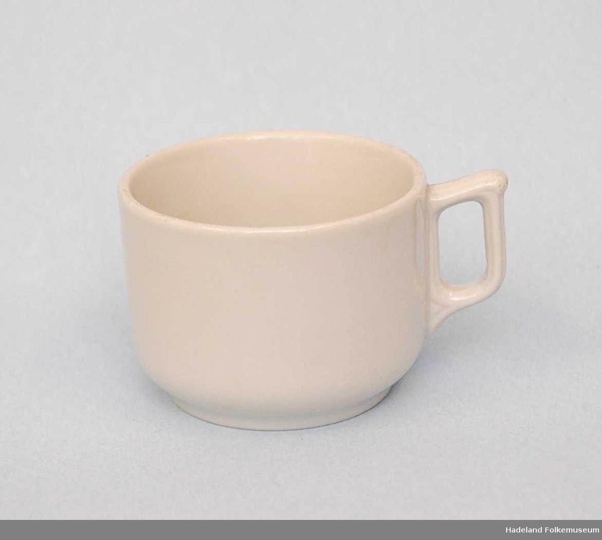 Drikkekar med hank til kaffe. Korpus er sylinderformet med fotring. Hanken har dekorstriper i godset.