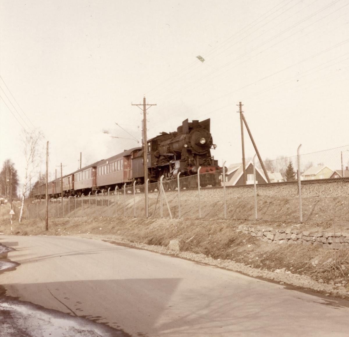 Persontog fra Dovrebanen ved innkjøringen til Hamar. Damplokomotiv type 30a.