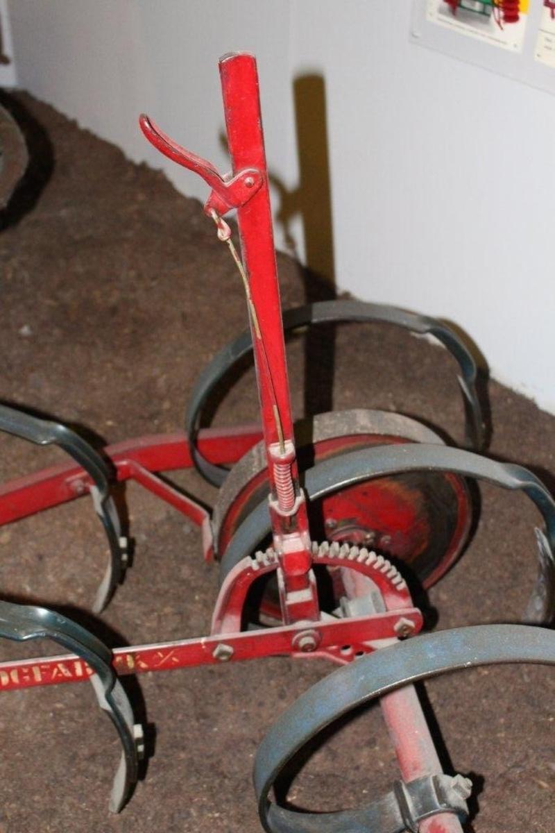 Ramme av vinkeljern. 9 tinder i 3 rader. To hjul i bakre rad, et mindre hjul fremme. Håndtak for regulering av arbeidshøyden.