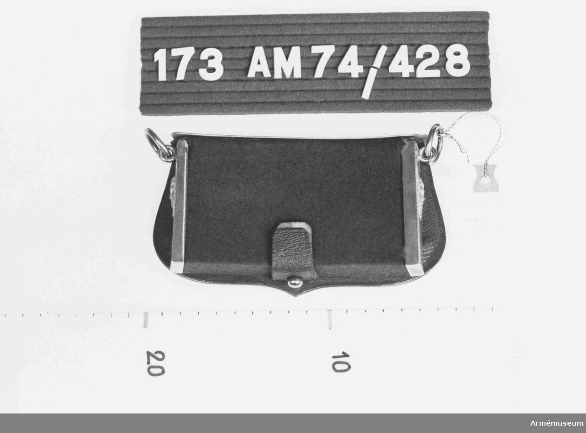 Väskan är klädd med blått kläde, skodd i sidorna med förgylld mässing. Sidostyckena har kvinnohuvud, Medusa. Locket i förgylld mässing, något sköldformat och ornerat i kanten med en  regelbunden bård ytterst och en bladslinga innanför. Emblem i  mitten i försilvrad mässing, visande en sköld med Sachsens vapen vilande på två st kanoner och fyra st fanor. Locket är  fodrat med rött läder och tillslutes med en tamp av rött läder  mot mässingsknopp. Hängs i två mässingsringar som är fästa på gavlarna.  Källa: Nr II Formations und Uniformierungsgeschichte.
