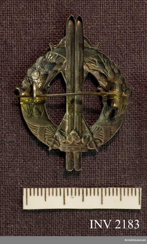 Samhörande nr är 2170-2188.Märke, skidlöpar-, silver, generalitet.Lagerkrans med tre kronor och ett par upprättstående skidor. Nål på baksidan för fastsättning.