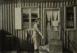 Kvinne utenfor et hus
