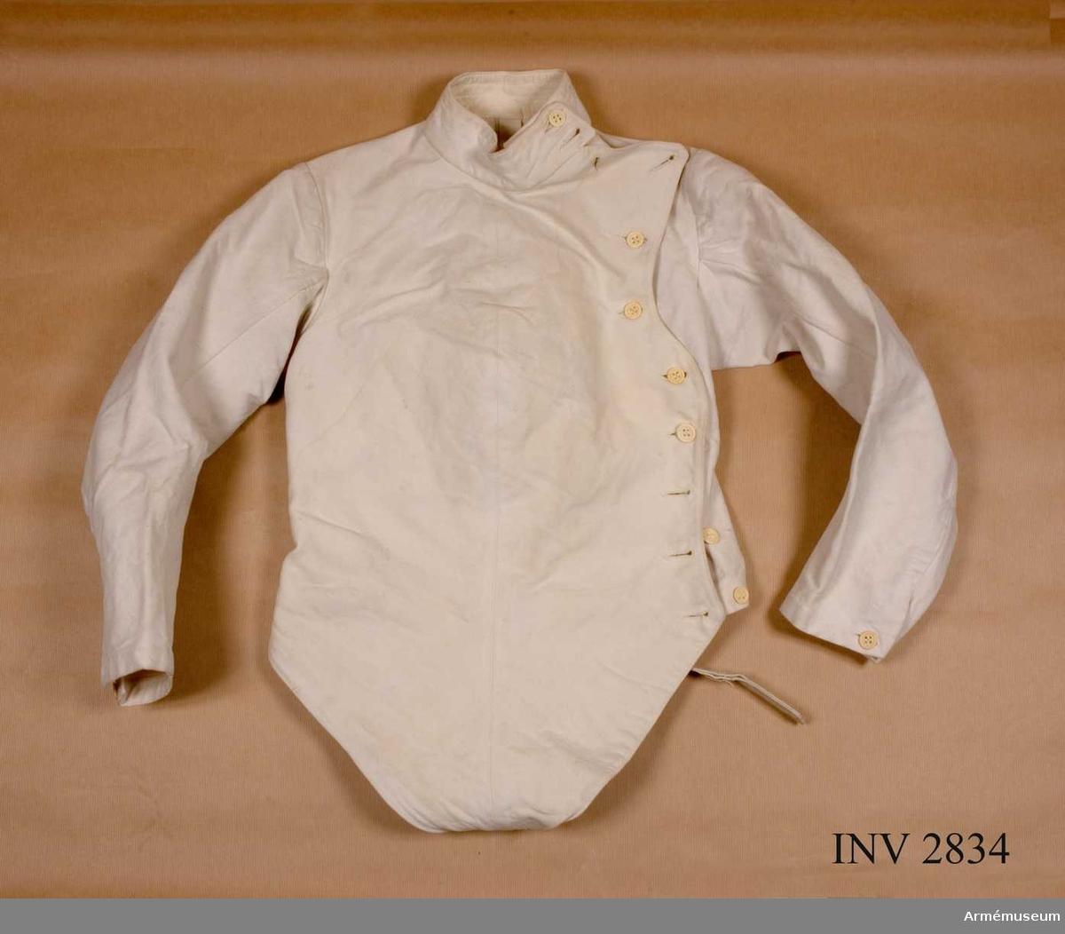 Av vit domestik, ett grovt bomullstyg. Knäppt på vänster sida med elva benknappar. Vadderat bröststycke. Långa ärmar med enkelt sprund nedtill knäppt med en knapp. Ståkrage. Framstycket i en spets nedtill, med en tamp att knäppa under bålen mot bakstycket. Används vid fäktning. Använd av major U.E.F. Lindberg på GCI åren 1922-1923 i egenskap av officer vid I 16.