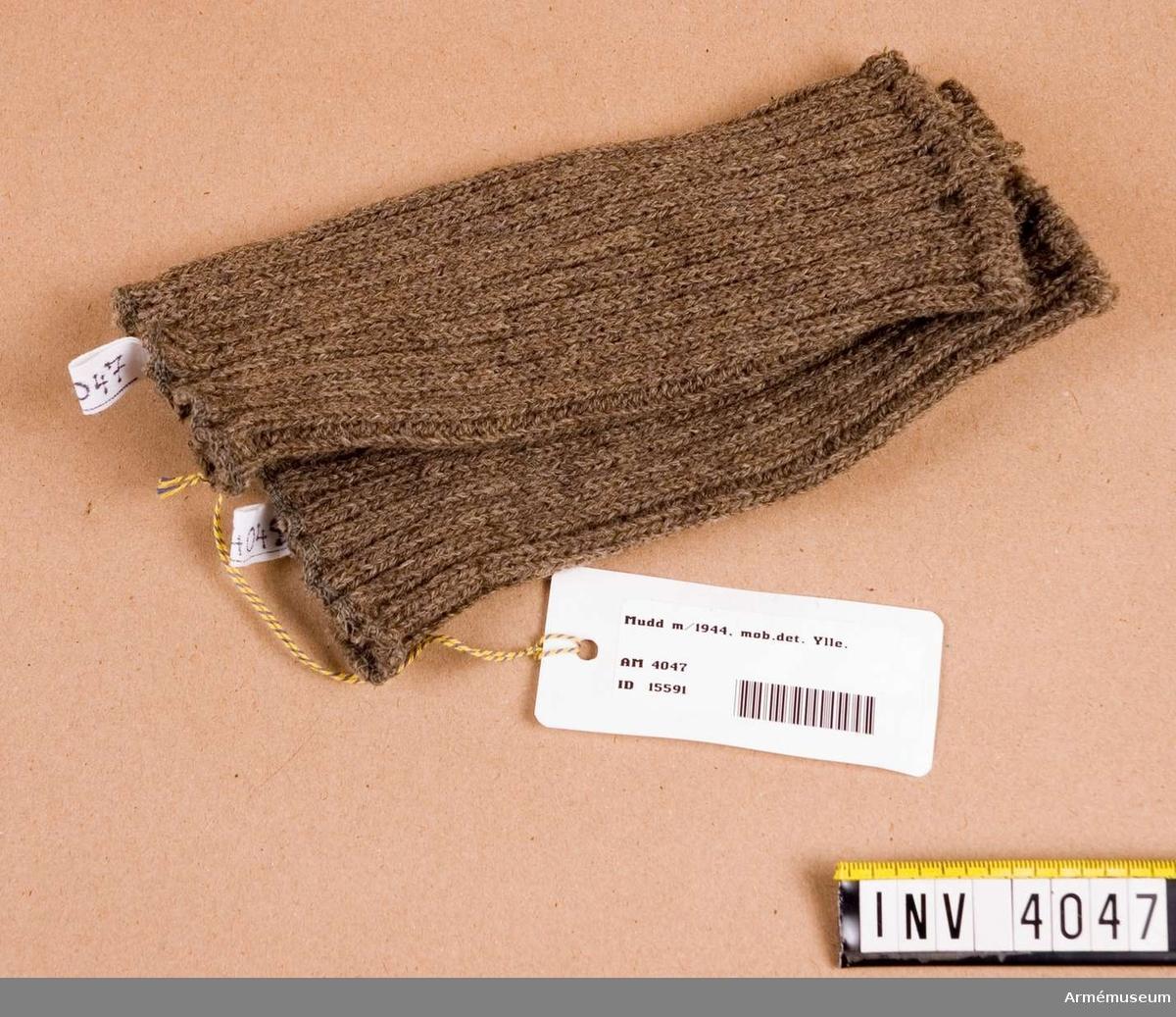 Obegagnat skick. Stickad av yllegarn i gråbrungrön färg. Maskinstickad i resårstickning. 20 mm från ena kanten är kanten ihopfäst.  Tummen skall träs i här.   Samhörande par: 4047-4048. Samhörande utrustning: AM 4038-4067.