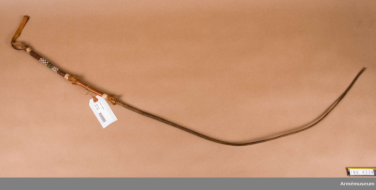 Piska, Fezzan, Libyen, Afrika.Skaft av brunt läder arbetat m läderremmar i rutmönster i färgerna brunt, vitt, svart och grönt. Slutar med en handrem. Stam: Arab. Insamlingsår 1960. Gåva av forskningsresande G Mobergs dödsbo, fru M Moberg, Narvav 7, 144 60 Stockholm.