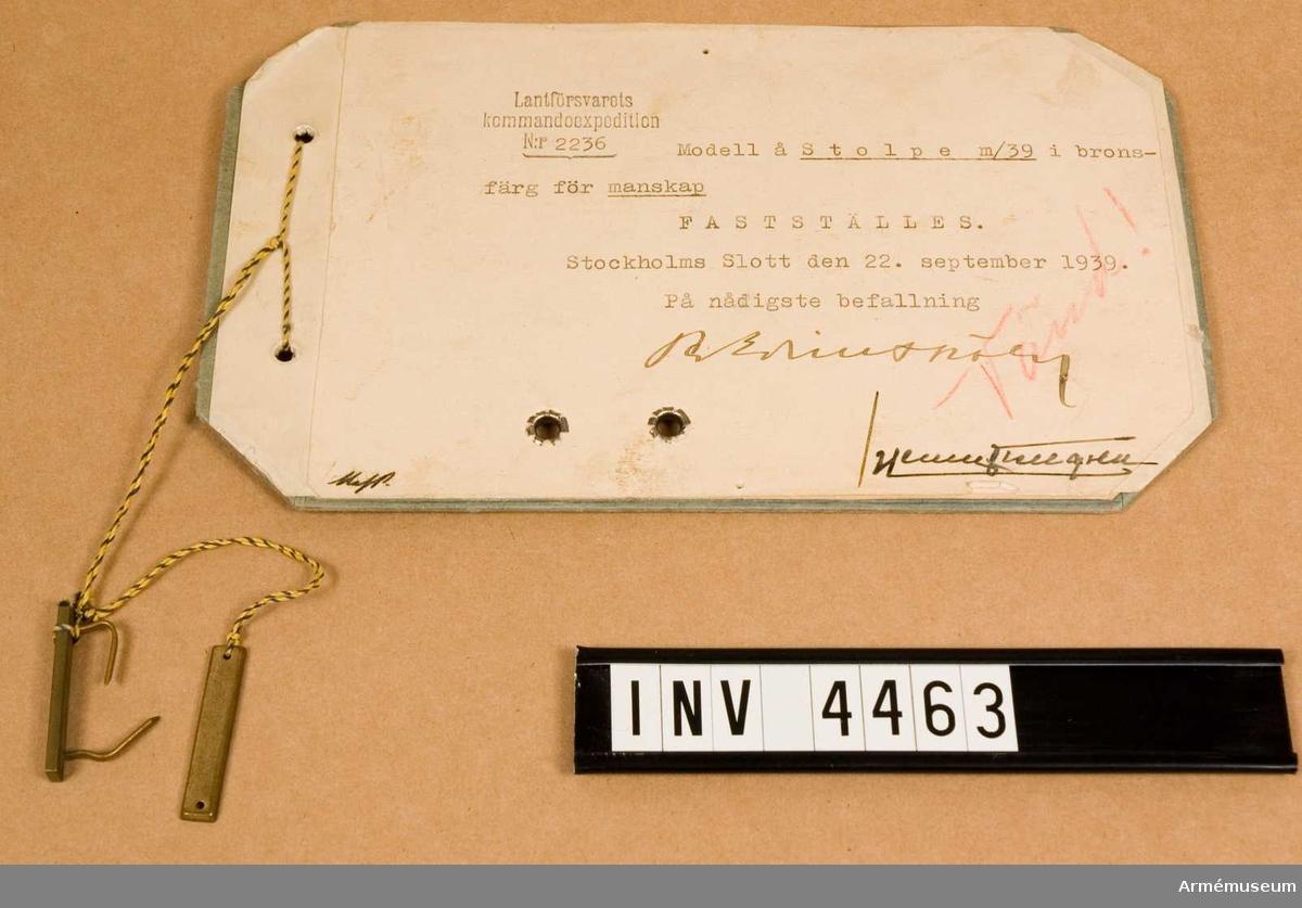 """Gradbeteckning m/1939, manskap.Av metall. På var klaff anlades 1-4 stolpar beroende på tjänstegrad. För fastsättning tillv. stolpen antingen m två syhål eller m två klammer, fastlödda på baksidan. Vidhängande etikett anger fastställelsedag: """"Stockholm Slott den 22. sept. 1939 Per Edvin Sköld /Henry Kellgren""""."""