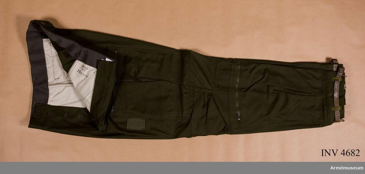 Fältbyxor m/1969, flygande personal. Storlek C 50. Jackan är tillverkad av olivgrön varpsatin, 50 % polyester och 50 % bomull. Denna fältbyxa samt tillhörande fältbyxor m/1969 flyg och vilka ingår i fältuniform m/1969 flyg, tilldelas arméns och marinens flygande personal, således ej personal vid flygvapnet. Den är försedd med två snedställda sidfickor, med spetsskurna lock knäppta med knapp och knapphål,  en bakficka på höger bakbyx med knapphålsslejf och knapp. Två  påstickade lårbensfickor med bakåtlagda veck samt blixtlås.  Högra lårbensfickan försedd med en insats av twills och består av tre insydda fack för magasin till kulsprutepistol och ett  för första förband. På fickans insida vid överkanten är en  cirka 6 cm bred skyddskant fastsydd. Vänster ficka saknar  insats och skyddskant. I nederkanten på varje byxben en  smalbensficka med blixtlås. Invid lårbensfickornas innerkanter  på varje byxben finns ett fästband av bomull för kartklämmor. Fast damask med hällor av syntetband genom vilka en läderrem med två löstagbara remhakar är trädd finns. Mitt fram och mitt  bak på damasken finns öljetter genom vilka remhakarna trädes  för att sedan fästas vid skodonen, den främre i snörningen, den bakre i stroppen i bakkappan. Knä- och grenförstärkningar samt hällor för livrem och hängselknappar finns. Samtliga knappar är av polyamid. Bakbyxorna är försedda med sprund och blixtlås över vaden från knäveck till nederkant. Märkning: På vänstra frambyxans insida (byxfickan) stämpel: Tre kronor 76 HAGA (firmanamn för tillverkaren AB HAGA-PRODUKTER, Örebro). På midjebandets insida finns vävd storleksetikett C 50.