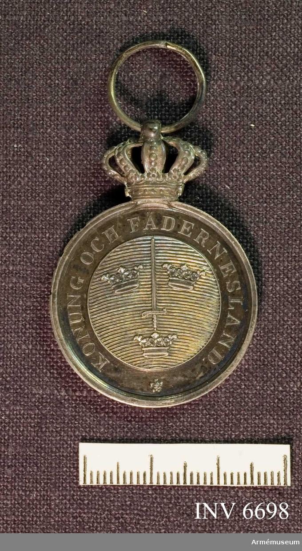 """På åtsidan ses på en glob Sveriges tre kronor med ett  upprättstående svärd och omskriften """"Konung och fädernesland"""",  på frånsidan inskriften """"För krigsmannaförtjänster"""". Medaljen är av silver och bäres i gult band med blå kanter."""
