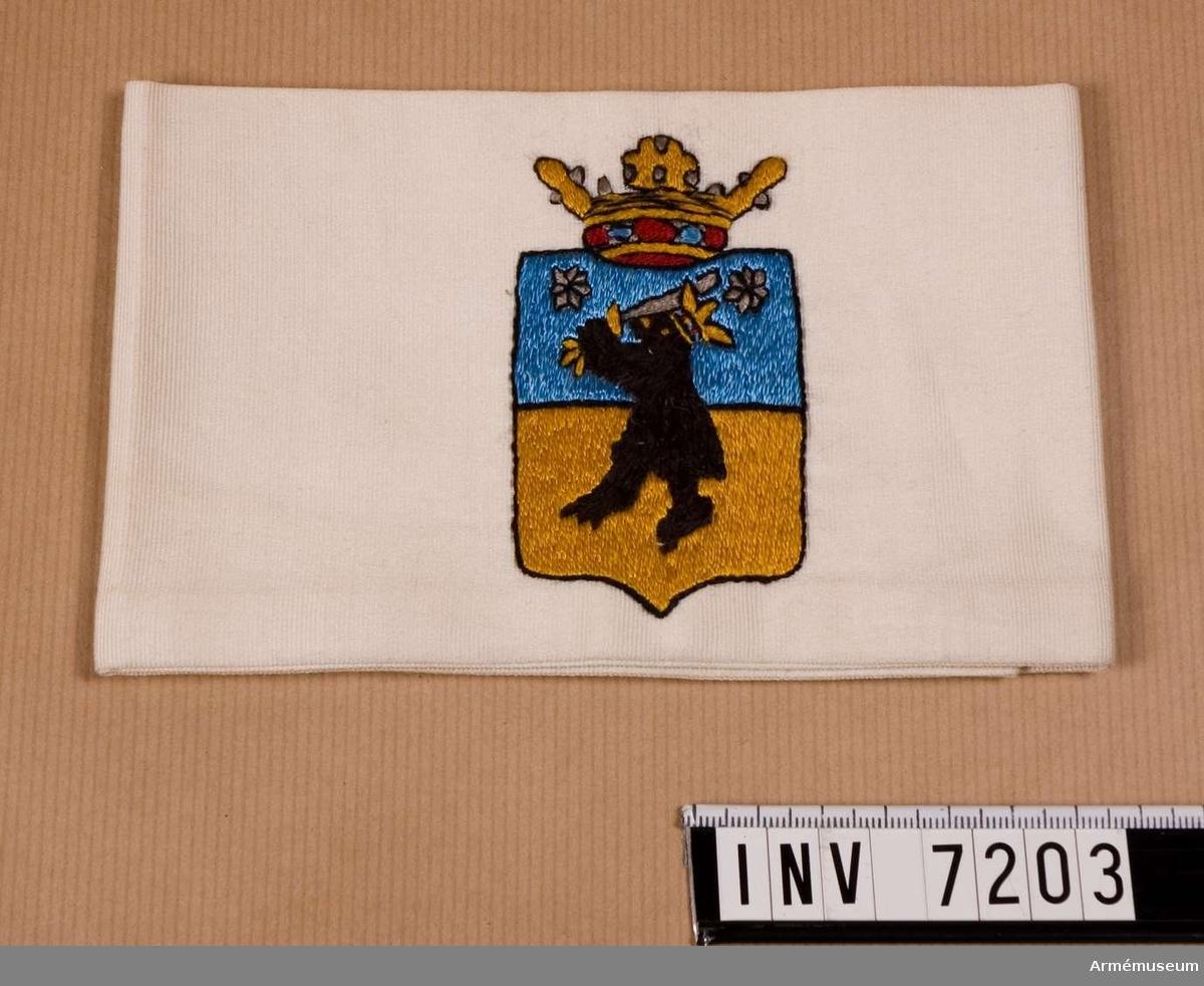 Armbindel, Björneborg, Finland. 1918. Sydd dubbel av vit sidenrips. På mitten ett broderat vapen för Björneborg.