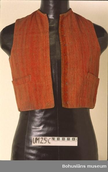 """Smalrandig väst i rött, svart, gråbeige och grågrönt, i en modell utan krage och med två horisontella stolpfickor. Tyget har inslag av ull- och lingarn och troligen varp av lingarn. Västen är fodrad med vitt (nedsmutsat, mörknat) linnetyg. Längs framkanten på vänster sida 10 hakar och på höger sida några cm in 10 metallhyskor. I halsen är västen kantad med en remsa av tyget. Fram- och sidor är skurna i ett stycke. Mitt bak finns två kilformade delar, som avslutas nertill med fodrade rektangulära former och sidstyckena (även de fodrade) ligger längst ner lösa ovanpå mittdelarna. På så sätt bildas där ett minimalt skört.  Enligt Knut Adrian Anderssons katalog I:11:4, i museets arkiv D 2 A:1, är västen del av en """"Karldräkt från Vingåker socken i Södermanland"""".  Angående givaren N P Hamberg och de sk Hambergska samlingarna som han skänkt till museet se Knut Adrian Anderssons katalog, I:141-143.  Hål vid nederkanten på vänstra framstycket, mycket litet rostigt hål vid nederkanten på högra framstycket. Blekt. Fodret mycket smutsigt.  Litt; Arnö-Berg, Inga, Folkdräkter och bygdedräkter från hela Sverige, Örebro 1976, sid. 103-106 (om Vingåkersdräkten, bild på Vingåkerdräkter).  Nylén, Anna-Maja, Folkdräkter ur Nordiska museets samlingar, Nordiska museets handlingar 77, Lund 1971, sid. 48-49 (om västar). Folkligt dräktskick i Västra Vingåker och Österåker, Nordiska museets handlingar 27, Uppsala 1947, sid. 77-79. Omkatalogiserat 1997-03-05 VBT  Ur handskrivna katalogen 1957-1958: Mansdräkt från Vingåker a) Långrock. Vit m. blå garnering kring  ärmar o hals. Malhål. ( 1600-1700 börj. av 1800-talet) b) Jacka. Vit. Bårder med bladornament.  Lappkatalog: 75"""