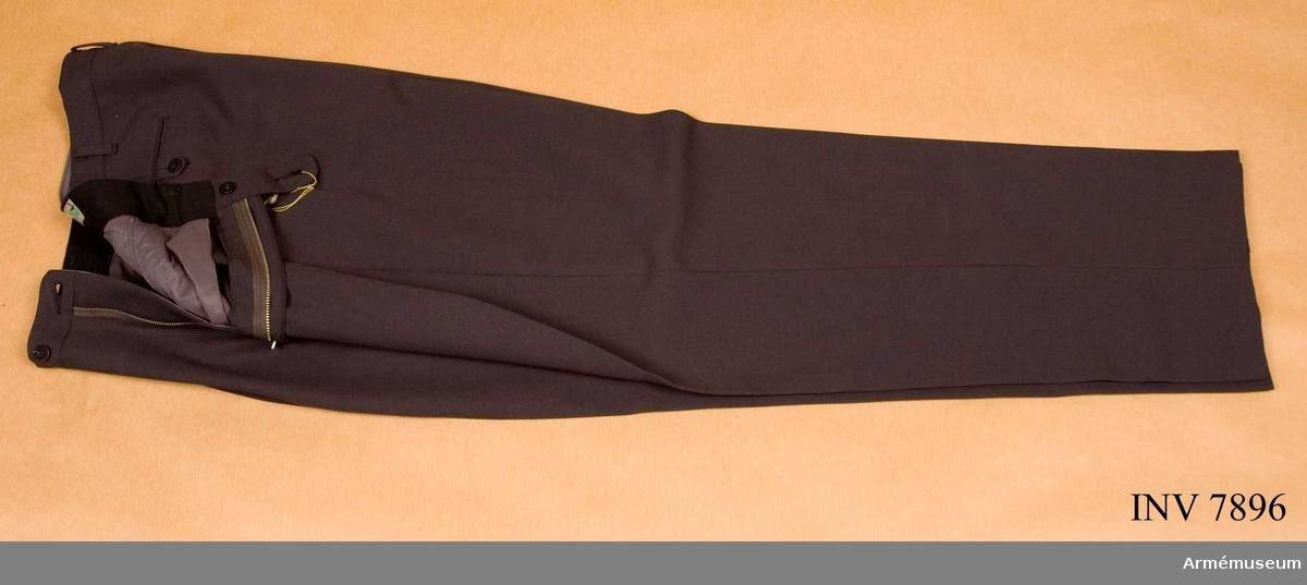 För Tygtekniska Kåren m fl. Till vapenrock m/1960. Byxorna är tillverkade hos CBV Karlskrona och märkta storlek C 50. Byxorna är sydda med raka ben utan uppslag, har två raka sidfickor och två bakfickor samt hällor för bälte. Midja 880 mm. Stuss 1060 mm. Benlängd 800 mm. Storlek C 50.