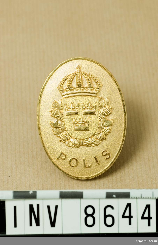 Höjd 55 mm. Bredd 40 mm. Vikt 30,5 g. Ovalt märke av mattförgylld metall med det lilla riksvapnet vilande på kvistar av ek och två korslagda spöknippen. Utmed den nedre kanten står det POLIS. Frånsidan är märkt MILITÄRPOLISEN Nr 2973. Anbringas på vänster sida av bröstet. Källa UNIA 1977 515. M 7673-577010.