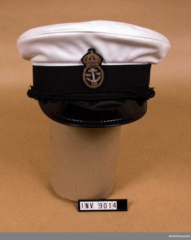 """Marinen / flottan (vit).Mösstommen på vilken monteras vit eller blå mösskulle. Mösstommen är överklädd med vitt tyg och försedd med ståndare, svettrem, svart lackskärm, svart mössband samt två uniformsknappar av storlek 3. Mössbandet är av resårband. Mössmärket 55 mm högt i guldbrodyr på underlag av mörkblått kläde, bestående av ankare med ankartåg omgivet av tre kronor, däromkring en oval tross med krona över. För värnpliktig skall ankaret vara av broderat silver. Ankaret är av broderat silver.Källa: UNI FL nr 6129.Inlånad till utställningen """"Kriget och könsrollerna"""" 1984-05-04 -- 1984-11-31 (sic)."""
