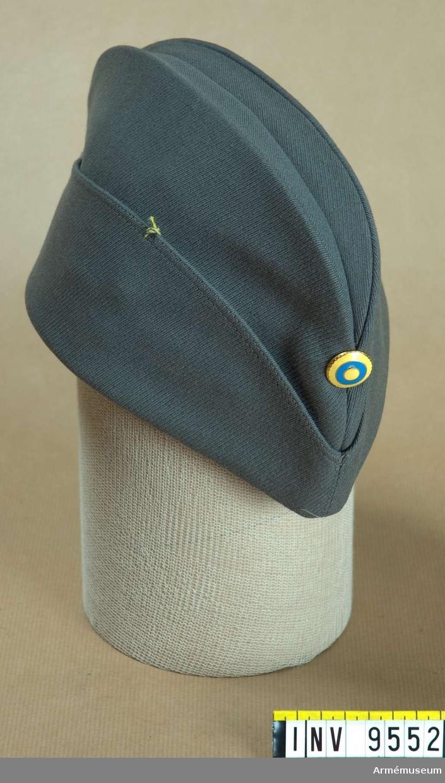 Båtmössa typ italiensk armémodell 1958. Av grått ylletyg med grått konstsidenfoder och ljusbrun  svettrem av konstläder. Mitt fram det svenska  nationalitetsmärket m/1941.