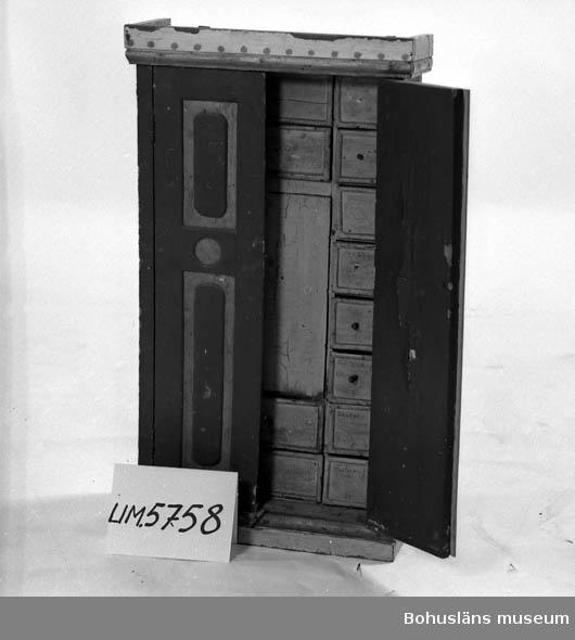 Ur handskrivna katalogen 1957-1958: Kryddskåp H. 87, Br. 47,5 Dj. 21,5 cm; framtill 2 dörrar, m. vardera 2 speglar; bakom dem i mitten ett litet skåp och runt om detta 20 draglådor; på framsid. gråmålade; 11 lådor saknar handtag. På utsid. är skåpet grönmålat. Skamfilat.   Lappkatalog: 82
