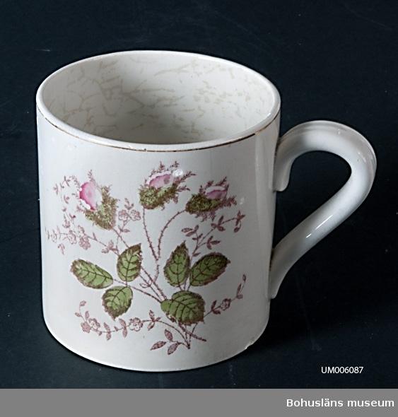 """Cylindriskt kärl med en hänkel. Vit med två rosbuketter i grönt och rosa (mossrosor). Vid mynningen är det en guldrand. Under botten står det intryckt i massan: """"GÖTEBORG"""" samt """"5"""", """"03"""" och """"9"""". I rött står det skrivet """"137  16"""". Muggen är krackelerad samt har små urslag.  Ölost (eller ölsupa, ölsoppa) är en traditionell bohuslänsk dryck som bygger på svagdricka och mjölk som kokas och vispas. Recept se UM005098  Ur handskrivna katalogen 1957-1958: Ölostmugg, """"Göteborg"""" Mynningsdiamet.: c:a 12 cm. H.: c:a 12,5 cm. Vitt porslin med törnrosbuketter i grönt och tött. Guldrand. Hel.  Lappkatalog: 62"""