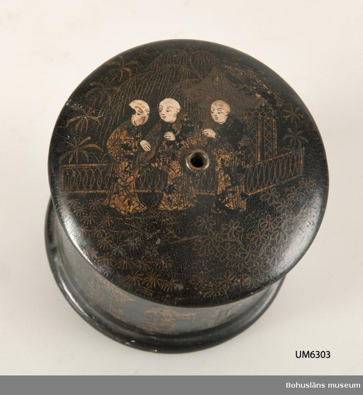 571 Användningstid *1880-1950?  Cylinderformad med välvt lock och fotring. Locket har ett hål på mitten där tråden löper igenom. Lackarbete med svart botten och figurscener målat i guld och beige. Enligt uppgift från Kina eller Japan. Något defekt kant på nederdelen.  Ur handskrivna katalogen 1957-1958: Svart lackask med lock, för tråd H. 6.7 cm Diam 6.6 cm. Hål i locket för trådända. Mytologiska scener i guldfärg Kina & Japan  Lappkatalog: 10