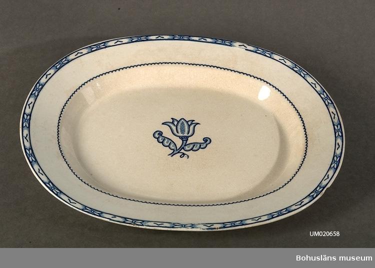 """Stiliserad blå kant samt tulpanliknande blomma i spegelns mitt. Del till servis """"Holland"""" formgiven av Wilhelm Kåge, Gustavsberg."""