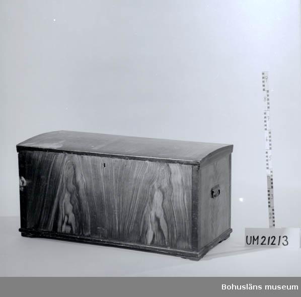 """Ådringsmålad kista; måleriet liknar mest valnötsimitation, alla hörn och kanter mörkare ådringsmåleri. Locket svagt välvt. Profilsågade brädor som """"fötter"""" i de fyra hörnen, höjd ca 9 cm. Lockförsedd låda s.k. läddika inuti på högersidan; gråmålat innandöme.  """"Läddika"""" är namnet på en liten lockförsedd låda placerad längs ena kortändan högt uppe vid överkanten i en kista. Läddikan användes för förvaring av värdefulla småsaker. Läddikor fanns redan i medeltida kistor. På engelska kallas lådan för """"ledge"""".   UMF 1:7"""