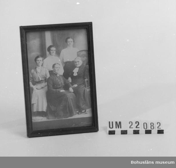 410 Mått/Vikt ! 0,15 KG, H 18, B 12,8, TJ 1,5 CM 594 Landskap BOHUSLÄN  På bilden sitter tre kvinnor i högtidskläder i Ture Niléns fotoatelje i Uddevalla.  Ramen är brunmålad.        UMFF 77:8