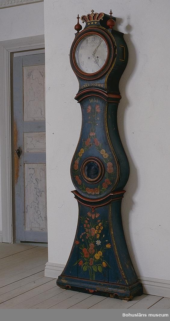 """Fodral med insvängt mittparti samt utsvängt basparti nertill. Upptill runt urverkshus, upptill prytt med sluten krona flankerad av två svarvade röda knoppar. På urverkshusets sidor kvadratiska fönster samt på dörren till loden runt glas. Glaset framför urtavlan är sekundärt. Originalglaset finns, men är sprucket i fyra delar. Blågrön grundfärg, röda lister och krona i gult och rött. På nederdelen målad bukett av rosor, tulpaner i rött och gult samt en vit prästkrage? samt grönt bladverk. På dörren en girland av rosor och tulpaner i rött och gult samt grönt bladverk. Längst upp på dörren är årtalet """"1855"""" målat i gult. Strax under urverket glas initialerna """"T.A.L.S.  J.A.D."""" i fraktur. Urverket ursprungligt märkt """"A.A.J. Mora"""". Rund, vit urtavla med arabiska siffror med profilerade mässingsvisare. Pendel med mässingsskiva. Två lod av järn med avsmalnande cylinderform. Profilerad vev för uppdragning."""