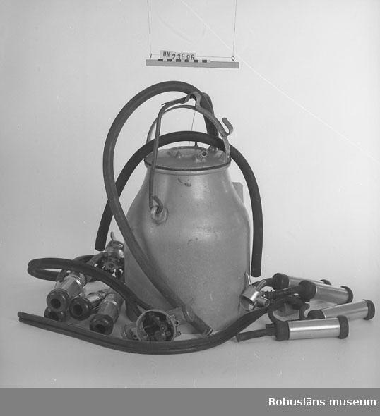 """En pulsator med fyra spenkoppar, en mjölkhink med lock samt en slang i två delar. Pulsatorn är helt gjord i metall och är märkt """"MANUS TYPV MADE IN SWEDEN"""". Den sitter ihop med spenkopparna genom två slangar - en för vakuumtryck och en för mjölk. Pulsatorn fästs i mjölkhinkens lock. Slangarna till spenkopparna är märkta: """"ALFA LAVAL 20012 MADE IN SWEDEN"""". Nederdelen på spenkopparna är märkta: """"MANUS 953041-1 944/57 5"""" (eller 2 eller 3). Spenkopparna sätts på kons fyra spenar. Mjölkningen sker genom vakuum. Med en vakuumpump skapas vakuum i ledningen och mjölken sugs ut. Vakuumet erhålls från ett rör i ladugården ovanför kons huvud. Med hjälp av pulsatorn släpps luft ut med jämna mellanrum och en massageeffekt uppstår i spenkopparna. Mjölken sugs ner i mjölkhinken. De två lösa slangarna går troligen till vakuumledningen. Den ena spenkoppens mjölkslang är lös. Gummislangarna är spröda.  Litteratur: Nordenborg, M.O. Lilla jordbruksboken, Stockholm 1946, sidan 192 ff. Berglund, Nils, Andersson, Yngve, Lantbruksmaskiner och redskap, Stockholm 1945, sidan 328 ff. Neg nr. UM152:11."""