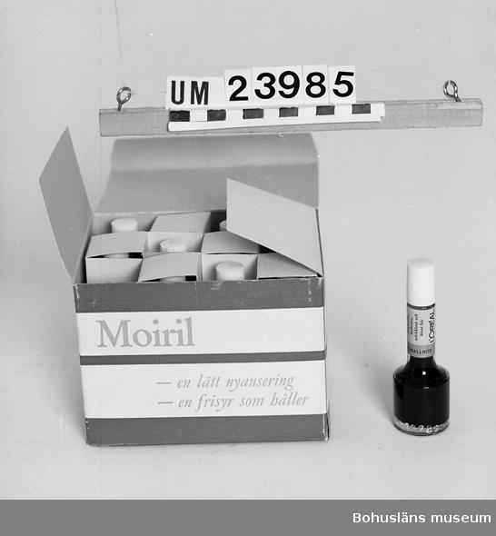 """594 Landskap BOHUSLÄN  Papplåda med vit och lila dekor och text i grått: """"Moiril, en lätt nyansering, en frisyr som håller. Förvaras svalt"""". Innehåller tolv flaskor för korallröd färg. Föremål från Brorssons Damfrisering i Kungshamn, se UM023941."""