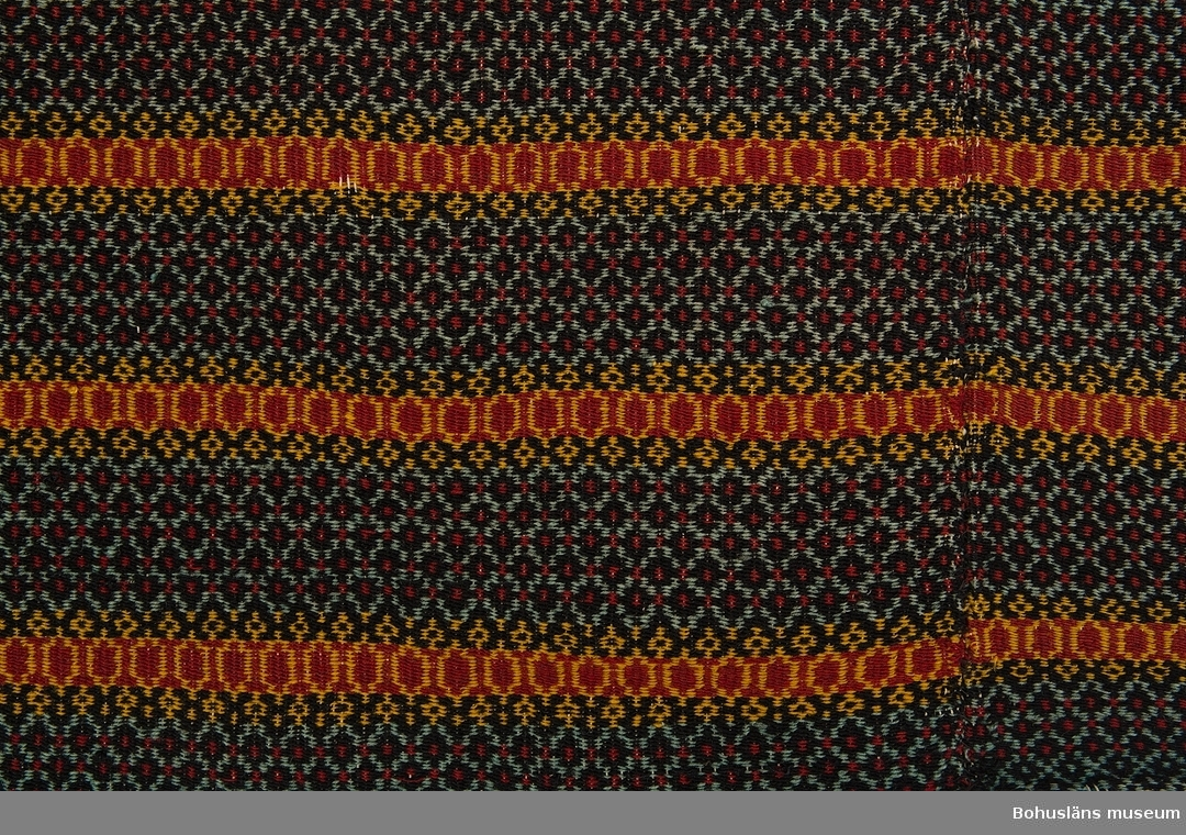 Handvävt täcke gjort i två våder, ihopsytt på mitten med längsgående söm. Med varp av bomullsmattvarp och mönsterinslag av ullgarn. Småmönstrat i bunden rosengång solvad på 3 skaft. Mönstret består av omväxlande smala och breda bårder som återkommer i en regelbunden randning. I de smala ränderna är färgerna gult och mörkrött, i de breda är bottenfärgen blåsvart och mönsterfärgerna mycket ljust blått, mörkrött och gult. Inslagsgarnet färgat med syntetfärg (utom möjligen de mycket ljust blå). Täcket fanns i museet på 1980-talets andra hälft.