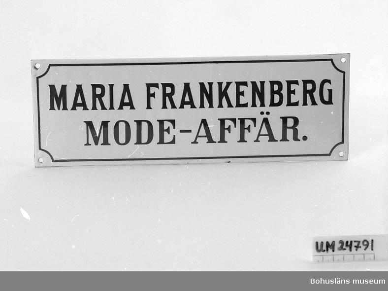 """Emaljerad. Vit bakgrund, blå text: """"MARIA FRANKENBERG MODE-AFFÄR."""" Blå ram runt texten.  Modisten Maria Frankenberg (1858-1938) startade den första modeaffären hösten 1886 på Asplundsgatan. Därefter innehade hon modehandel på Norra Drottninggatan 1, Uddevalla, Maria Frankenberg Mode-affär. Affären övertogs av bl.a. Sigrid Hansson efter Frankenbergs död och hette därefter """"Maria Frankenbergs Eftr. Modeaffär Uddevalla"""".  Se även UM022807:1-2; skyltar från samma modeaffär."""