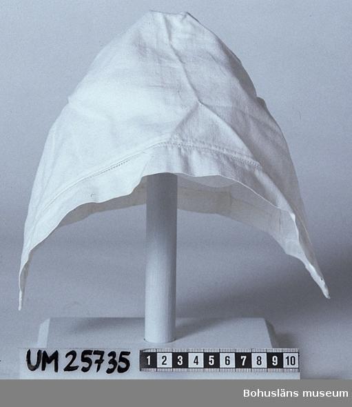 Hätta av vitt linne, av en rektangulär tygbit, fållad med symaskin, därefter dubbelvikt och sydd samman för hand längs ena sidan som är mitt bak på hättan. Fyra handsydda veck i nederkanten. Innanför en påsydd, dubbelvikt tygremsa som utgör mössans framkant finns ett band med hålsömsmönster. Del till Bohusdräkt se UM025730 - UM025734, UM025736 samt UM025738. Övrig information och litteraturlista se UM025730.
