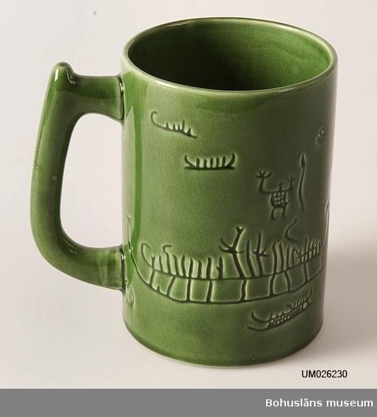 """Grönglaserad cylinderformad mugg med handtag med inpressad dekor av hällristningar efter förlagor av dylika i Tanums socken, Bohuslän. I botten märkt i godset """"Hällristningar i Tanum Bohuslän"""" samt  som firmamärke en vas på båda sidor av vars hals står """"SYCO keramik"""" och därunder """"Sweden"""""""