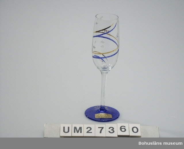 """*Diam. avser kuppans bredaste del.  Smalt glas av klart glas på hög fot. Fotring av blåmarmorerat glas, kuppan dekorerad med två parallella linjer i guld och blått som löper runt glaset. Dekorer av strödda klisterstänk/klickar. Klistermärke på kuppan.  """"Glas år 2000 Champagneglas använt av undertecknad på nyårsfest 1999/2000 hos bagarmästare Gösta Dahlskog och hans hustru Ulla, Bangatan 8 i Uddevalla, innehavare av Dahlskogs Bageri, Wienerkonditoriet och Princens konditori, alla i Uddevalla.  Värdpar samt sju gäster. Varje glas hade försetts med respektive  gästs namn och """"2000"""", liten reklamlapp från säljande affär, Rosie Design, Sankt Mikaelsgatan 2, Uddevalla.  Detta glas användes under aftonen för dels vitt vin dels champagne (välkomst- och 12-slagstid). Till middag serverades färsk hummer, marulk som varmrätt och hjortronparfait till efterrätt. Efter 12-slaget avhörde värdpar och gäster ett stort antal större och mindre fyrverkerier. Stellan Granat""""  Materialet ingår i den Millennieinsamling som Bohusläns museum gjorde inför millennieskiftet 2000 på initiativ från SAMDOK och Nordiska museet. Insamlingsgruppen bevakade, samlade in respektive köpte under perioden närmast före och efter nyåret olika trycksaker, bl a Bibel 2000 i nyöversättning, dagstidningar från den 31 december 1999, postorderkataloger, samhällsinformation som fanns att köpa eller spreds till allmänheten av myndigheter. Flera av katalogerna avser att visa klädmode, leksaksutbud, matvanor etc. vid tiden för millennieskiftet. Insamlingsgruppen gjorde personliga urval i butikerna i Uddevalla av det överflödande utbud av utrustning för firandet som särskilt tagits fram samt samlade in minnesföremål från det privata millenniefirandet.   Som en kuriositet och hälsning till framtiden skrev Insamlingsgruppen också ett brev till kommande museikollegor på Bohusläns museum.  Brevet är adresserat: """"TILL FRAMTIDEN BOHUSLÄNS MUSEUM BOX 803 451 19 UDDEVALLA"""" frankerat och avsänt den 31 december 1999 och ankomst"""