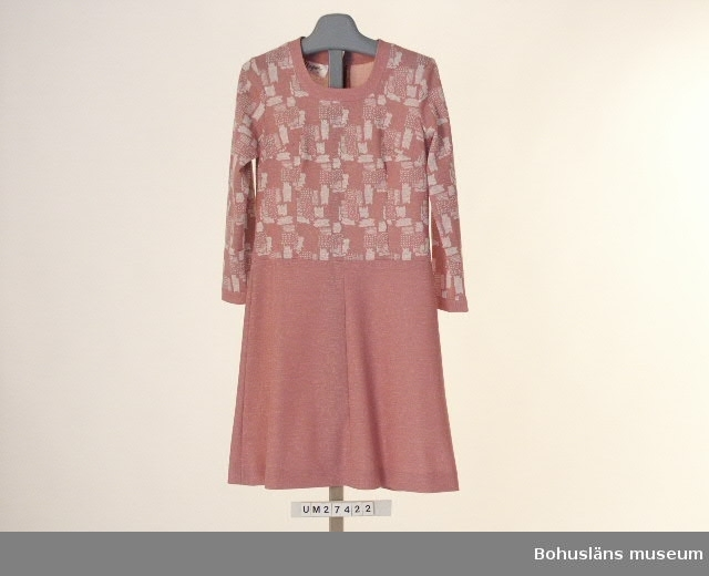 """Föremålet visas i basutställningen Uddevalla genom tiderna, Bohusläns museum, Uddevalla.  Rosa klänning  med lång ärm i jerseyliknande tyg med noppig yta. Överdel med gråvitt fantasimönster på rosa botten. Halvoval halsringning, kantad med enfärgat tyg. Bystveck och långa insparningar på framstycket. Ärmslut kantade  med enfärgart tyg. Lång dragkedja i ryggen. Lågt skuren enfärgad kjoldel i fyra våder som börjar i höfthöjd . Ofodrad. Etikett i halslinningen med med texten: """"Magna 40"""", skötseletikett med bl a tvättsymbol 40 grader.  I dragkedjan vidhängande pappersetikett i plastsnöre med texten: """"Magna på svart botten. På andra sidan med texten: Modell  F 11 Kvalité 5  553 Färg  3 Storlek  40 Varuinformation Pris: 269""""  Obegagnad vid förvärv.  Ur Nationalencyklopedin, NE.se: Terylen Terylen, en skrynkelhärdig textilfiber framställd av polyester urspr. varumärke, sedan 1955; av eng. terylene med samma bet.   För ytterligare uppgifter om förvärvet och övrigt material rörande Magnafabriken i museets samlingar, bl.a. dokumentation 1998, se UM027416."""