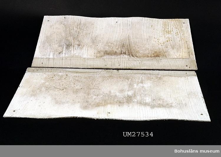 Två vita, räfflade eternitplattor med svagt vågformiga  långsidor. Sex borrade hål för uppsättning. Plattorna är ersättningplattor till givarnas hus på Åstol, Åstol 1:21.  Föremålet visades i utställningen Moderna skärgårdsbor på Bohusläns museum 2002. Utställningstext: Eternitplattor De första husen på Åstol kläddes med eternitplattor i början av 1950-talet, sedan blev det fler och fler under 50- och 60-talen. Fiskarna på Åstol anlitade snickare från Tjörn till att sätta upp plattorna som skydd mot väder och vind. Eternitplattorna krävde mindre underhåll än träfasader och hade en viss status, fast alla hade inte råd att klä sina hus. Idag är mer än hälften av husen klädda med eternit och dessa är nog en symbol för Åstol. Men i takt med att trä och snickarglädje anses mer estetiskt, försvinner allt fler av dessa grå och ljusgröna plattor.  Eternitplattorna  ingår i insamlingen i projektet Moderna skärgårdsbor, UM27511 - UM27595 och kommer från Åstol.  För övrigt material från Åstol, se UM27524-UM27538 och UM27566-UM27594; 27524 Tjörn Runt-teckning 27525- Vägskyltar, 9 st 27533 27534:1-2 Eternitplattor, 2 vita refflade  27535 Eternitplatta, 1 vitmålad slät 27536:1-2 Eternitplatta, 2 gröna 27537 Cykelkärra 27538 Matjordsäck, 2 st (omärkt) 27566- 28 barnteckningar över Åstol, indiv. inv.nr. 27593 27594 Skylt frikyrkan med gudstjänstaffisch Arkivet 9 uppsatser från skolbarnen i samband med teckningarna.  Se Bilagepärmen UM27534 för karta med huset markerat. För information om projektet Moderna Skärgårdsbor, se UM27511.  Litt: Sjöholm, Carina. Moderna skärgårdsbor i gammal kultur. Skrifter utgivna av Bohusläns museum och Bohusläns hembygdsförbund nr 73. Bohusläns museums förlag.  Avsnittet om Åstol s. 17 - 45..